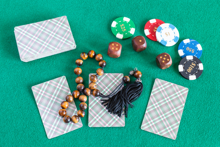 top view of card decks, wooden dices, casino tokens and worry beads on green table