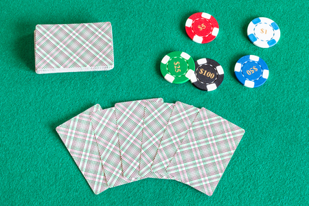 top view of card decks and casino tokens on green baize table