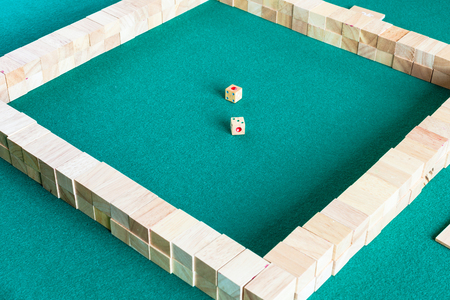 starting position of mahjong, tile-based chinese strategy board game on green baize table