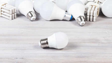 One white LED bulb light and energy-saving lamps on gray wooden board Banco de Imagens