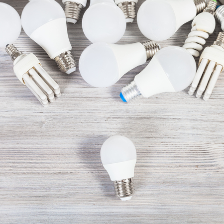 Top view of LED bulb light and many energy-saving lamps on gray wooden board