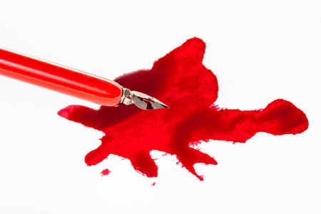 Above view of sharp nib in red dip pen over red ink stain on white paper