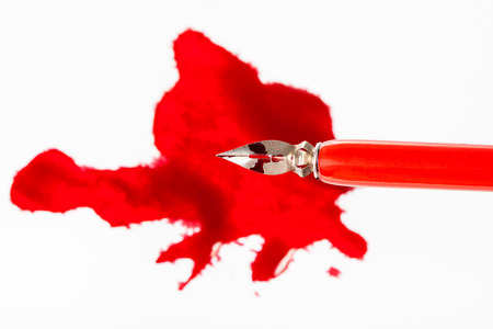 Top view of steel nib in red dip pen over red ink blot on white paper Фото со стока