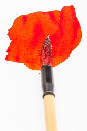 Red colored round goat hair tip of paintbrush for sumi-e ( suibokuga) painting in red blot on white paper close up