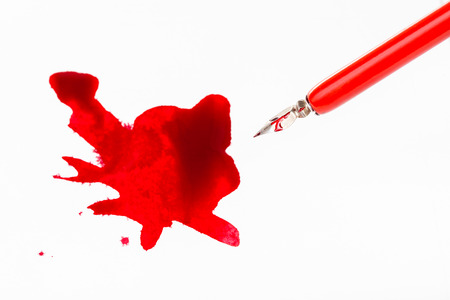 Top view of red nib pen over red ink stain on white paper