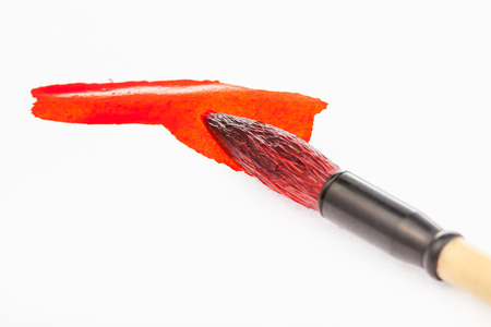 Red painted round goat hair tip of paintbrush for sumi-e ( suibokuga) painting in red stain on white paper close up