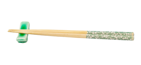 Side view of decorated wooden chopsticks served on chopstick rest isolated on white Stock Photo
