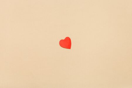 One little heart cut out of red paper on  from yellow navajo white pastel paper 版權商用圖片
