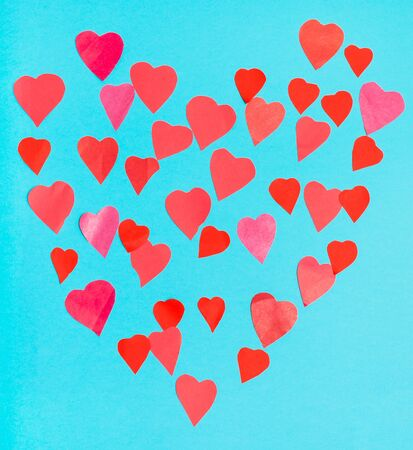 Collage of big heart filled by little pink and red hearts on blue  pastel paper