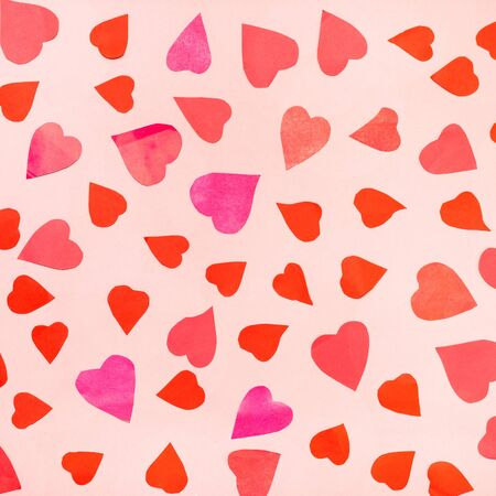 Collage of many hearts cut from pink and red papers on pink pastel paper
