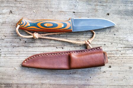 Handcrafted blackened steel knife with homemade epoxy and orange fabric handle with hand-sewn leather sheath on old wooden board