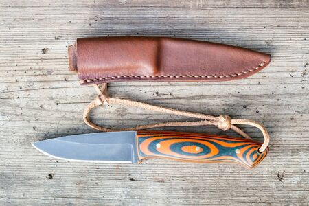 Hand forged blackened steel knife with homemade epoxy and orange fabric handle with to hand-sewn leather sheath on old wooden board Фото со стока