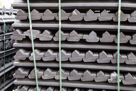 Stockpiles of gray rubber retainers for rails of tram track outdoors