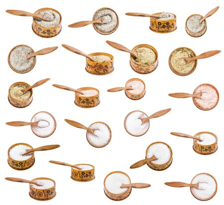 Set of wooden salt cellar with little spoon with various salts isolated on white