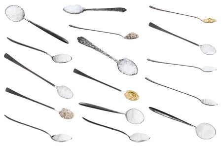 Collection from metal spoons with various salts isolated on white