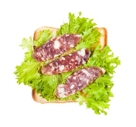 top view of open sandwich with toast and three slices of cured sausage and fresh green leaf lettuce isolated on white background