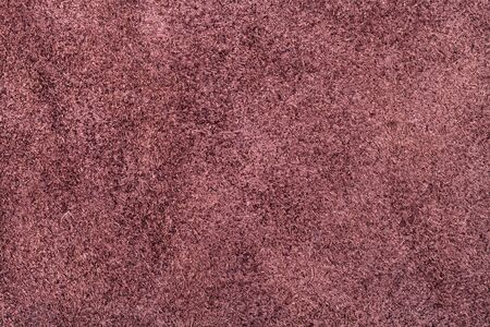 textured background from maroon brown suede close up
