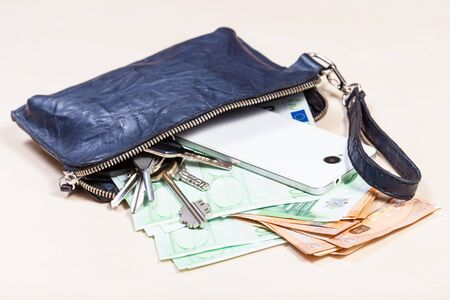 open blue leather wristlet pouch bag with bunch of keys, smartphone and various euro banknotes on pale brown table