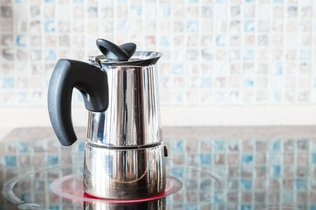 brewing coffee with pressure moka pot on ceramic electric range at home kitchen