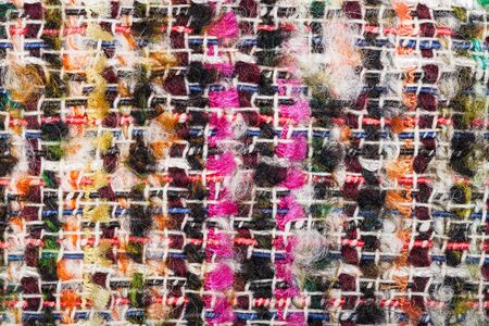 textile background - interlacing of color threads in boucle fabric close up