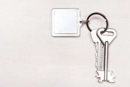 bunch of keys on keyring with blank white keychain on pale brown table