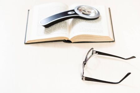 reading book with low vision - spectacles and magnifying glass on open book on pale table (focus in the foreground)
