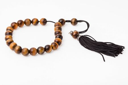 worry beads from tiger's eye gemstones on white paper background