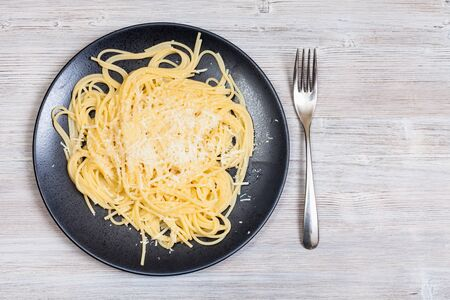 italian cuisine - top view of spaghetti al burro e parmigiano (pasta with butter and cheese) on black plate and fork on gray wooden background with blank copyspace Banco de Imagens
