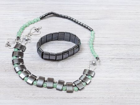 needlecraft background - handcrafted necklace from green jade, black hematite and silver beads and hematite bracelet on gray wooden board with copyspace Foto de archivo