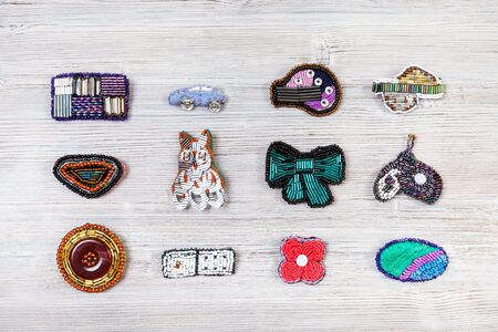 needlecraft background - top view of various handcrafted embroidered brooches on gray wooden board