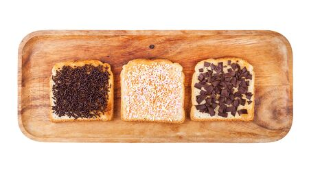 top view of various dutch sweet open sandwich with toast and toppings from chocolate sprinkles on wooden plate isolated on white background
