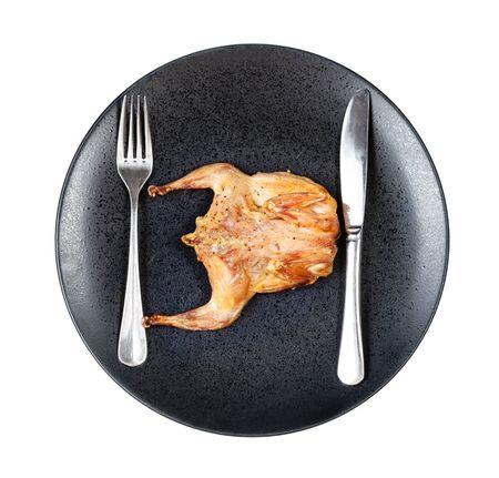Draufsicht auf gebratene ganze abgeflachte Wachteln mit Gabel und Messer auf schwarzem Teller isoliert auf weißem Hintergrund