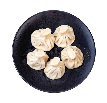georgian cuisine - top view of five boiled khinkali on black plate isolated on white background