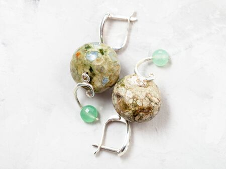 hand crafted silver earrings with rhyolite and nephrite beads on gray concrete background