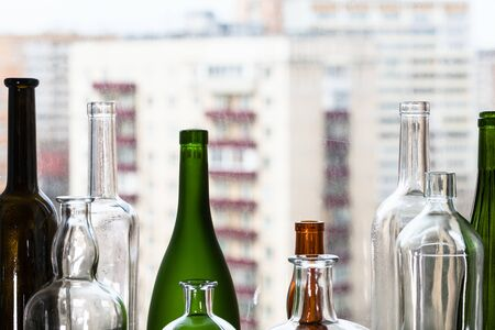 various empty bottles and view of apartment houses through home window on background