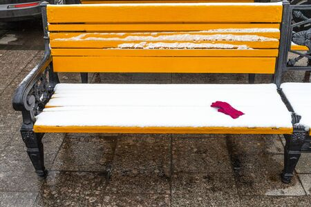 yellow wooden bench covered by snow with red female glove on Manezhnaya square in Moscow city in winter