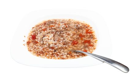 buckwheat soup in white soup plate with spoon isolated on white background
