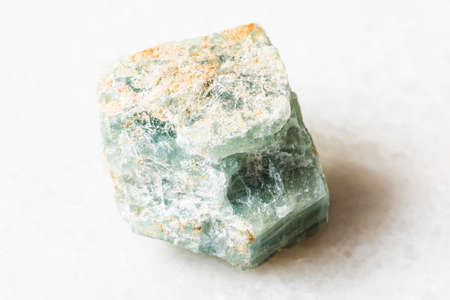 closeup of sample of natural mineral from geological collection - raw Apatite rock on white marble background