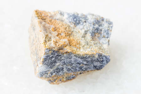 closeup of sample of natural mineral from geological collection - unpolished Corundum rock on white marble background Stock fotó
