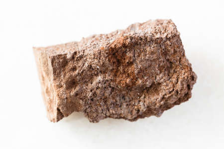 closeup of sample of natural mineral from geological collection - rough Bauxite rock on white marble background from Ukraine Stock fotó