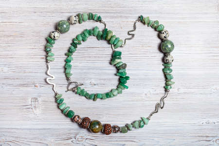 top view of handcrafted necklace from tumbled green aventurine gemstones, cracked agate, aplite, rhodonite and rudraksha beads on gray wooden table