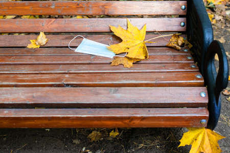 dropped medical face fask and yellow maple leaves on wooden bench in city park on autumn day Imagens