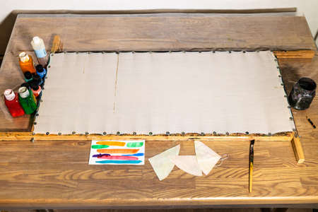 empty canvas fixed to wooden frame on table at home prepared for batik painting Banque d'images