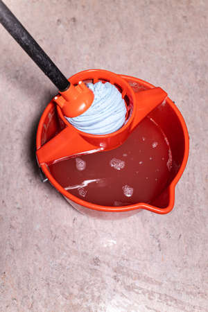 top view of squeezing mop in red bucket with dirty water at home Banque d'images - 163119373