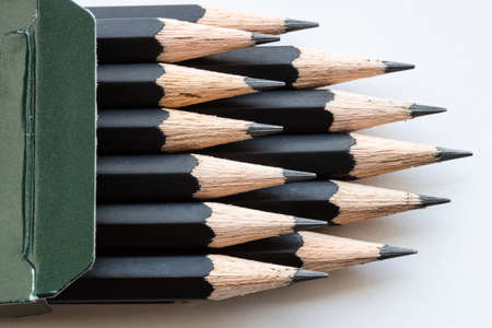 sharp tips of set of black graphite pencils close up in green cartboard box on white background