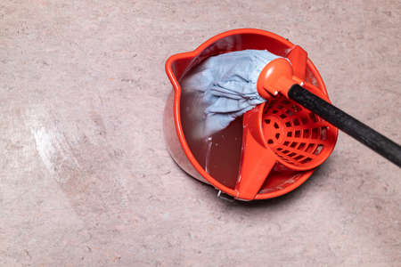 top view of mop in red bucket with dirty water at home