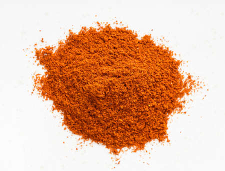 top view of pile of chili powder from cayenne pepper close up on gray ceramic plate Imagens
