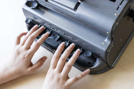Moscow, Russia - June 5, 2021: fingers touch of Perkins Brailler braille typewriter. The first Perkins Brailler was produced in 1951 by David Abraham, teacher at the Perkins School for the Blind