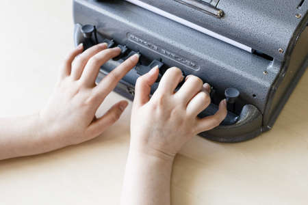 Moscow, Russia - June 5, 2021: hands types on Perkins Brailler braille typewriter machine. The first Perkins Brailler was produced in 1951 by David Abraham, teacher at the Perkins School for the Blind Éditoriale