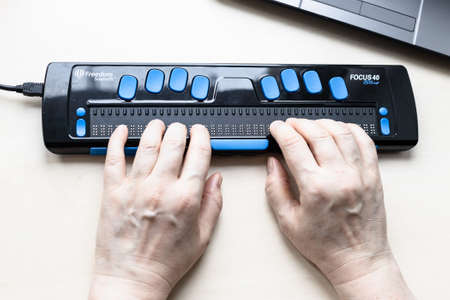 Moscow, Russia - June 5, 2021: female hands touch of Focus 40 Blue Braille Display. Freedom Scientific is the largest manufacturer of assistive technology products for blind and low vision people Éditoriale